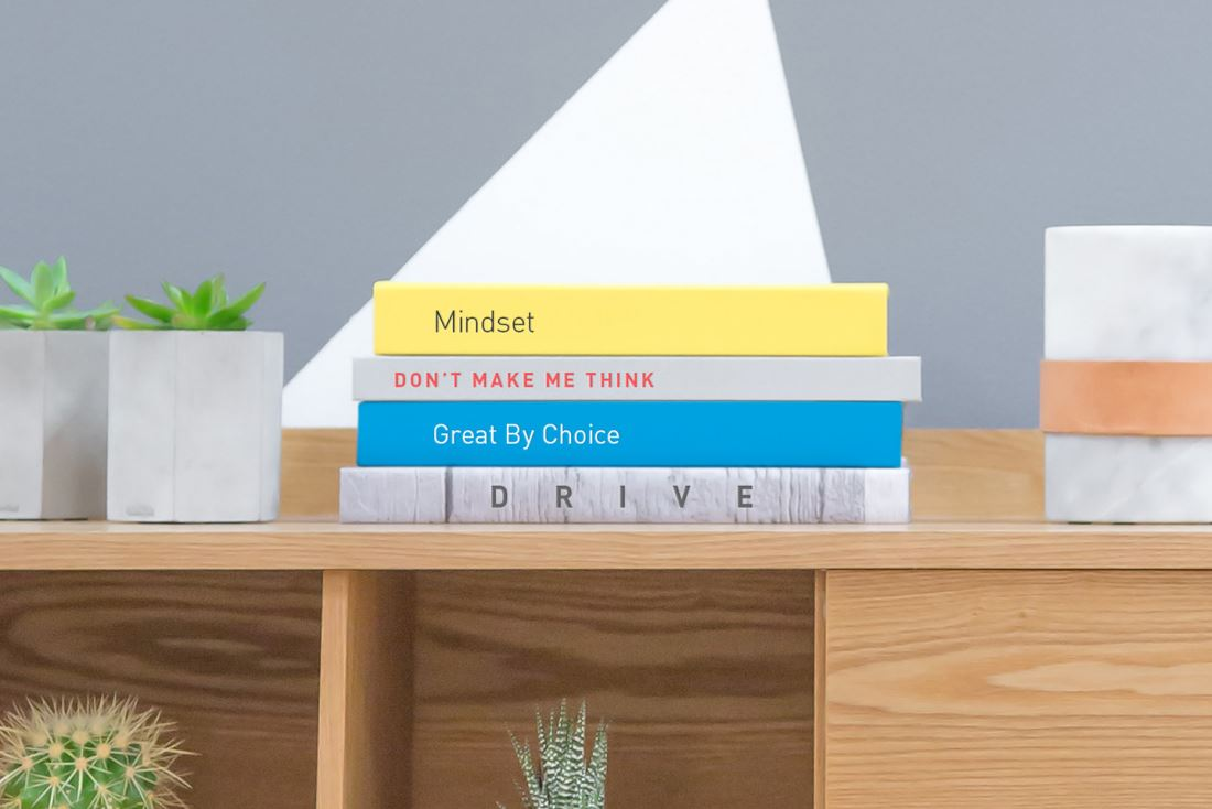 Three books stacked on a shelf surrounded by plants.