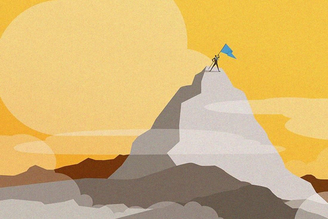 Man holding a flag on top of a mountain