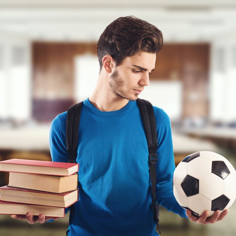 Student-athlete deciding between a stack of books and a soccer ball.